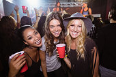 Portrait of female friends with disposable cups enjoying music in nightclub