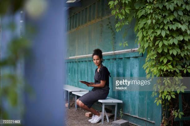 Portrait of female gardener holding digital tablet while sitting on bench