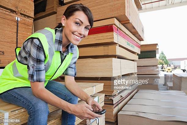 Portrait of female industrial worker using cell phone while sitting on stack of wooden planks