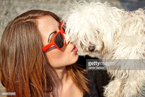 Portrait of female kissing a puppy