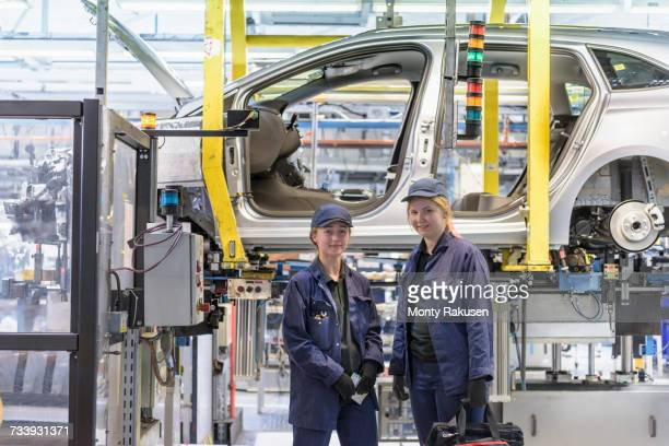 Portrait of female maintenance engineers working on production line in car factory