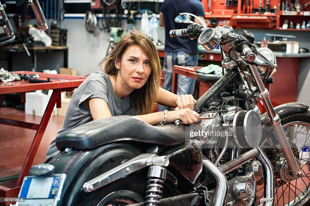 Portrait Of Female Mechanic In Motorcycle Workshop Stock