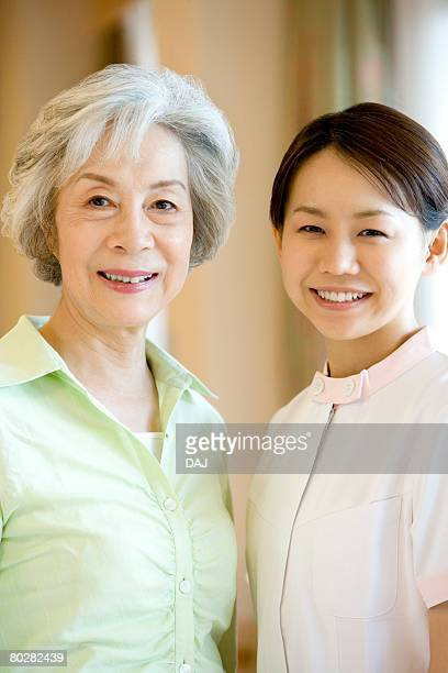 Portrait of female nurse and senior woman smiling and looking at camera, differential focus