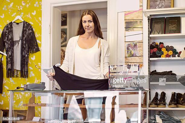 Portrait of female owner with evening gown standing at checkout counter in boutique