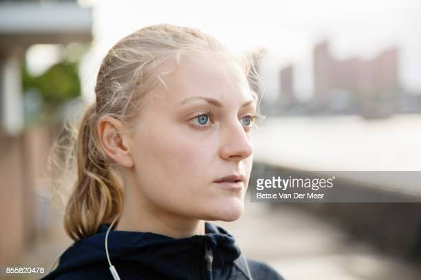 Portrait of female runner looking out over city.