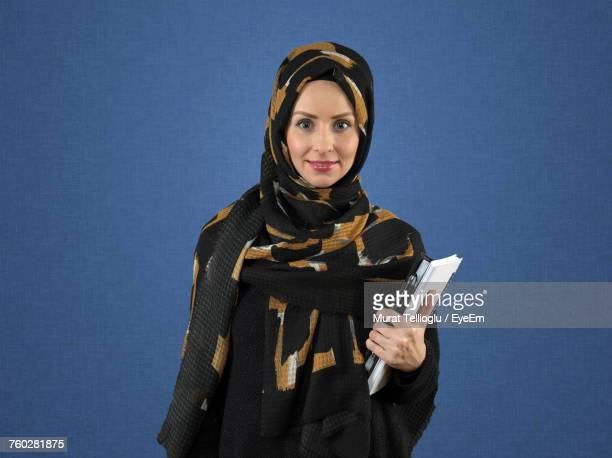 Portrait Of Female Student In Hijab Holding Book While Standing By Blue Wall