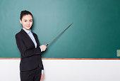 portrait of female teacher pointing to chalkboard.