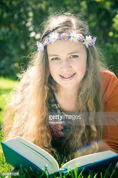 Portrait of female teenager lying on meadow with a book