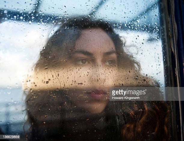 portrait of female through rain covered window