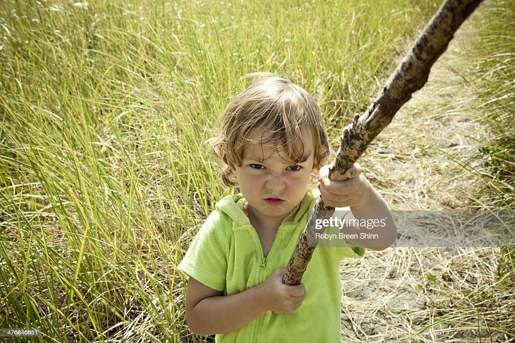 Portrait of female toddler holding long stick : Stock Photo