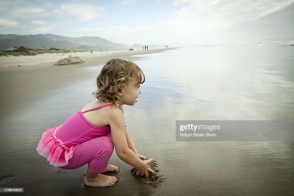 Portrait of female toddler playing in sand : Stock Photo