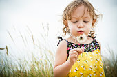 Portrait of female toddler with dandelion clock