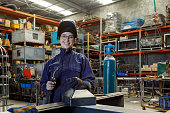 Portrait Of Female Welder In Factory Wearing Protective Safety Gear