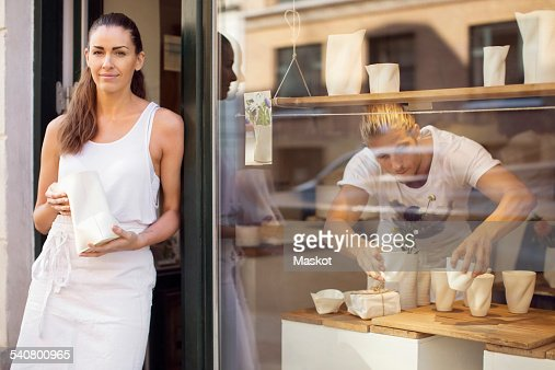 Portrait of female worker standing on doorway while male colleague working in workshop