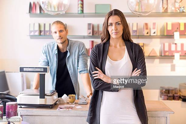 Portrait of female worker with colleague standing in candy store