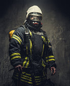 Portrait of firefighter in oxygen mask over grey background. Studio shoot.