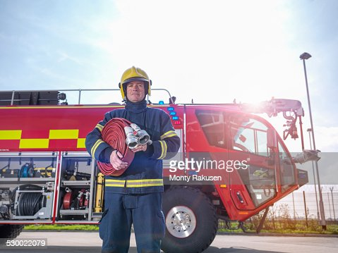 Portrait of fireman in front of fire engine in airport fire station