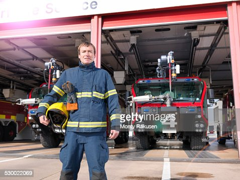 Portrait of fireman in front of fire engines in airport fire station