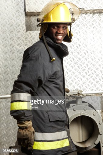 Portrait of fireman in front of water pump