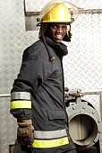 Portrait of fireman in front of water pump
