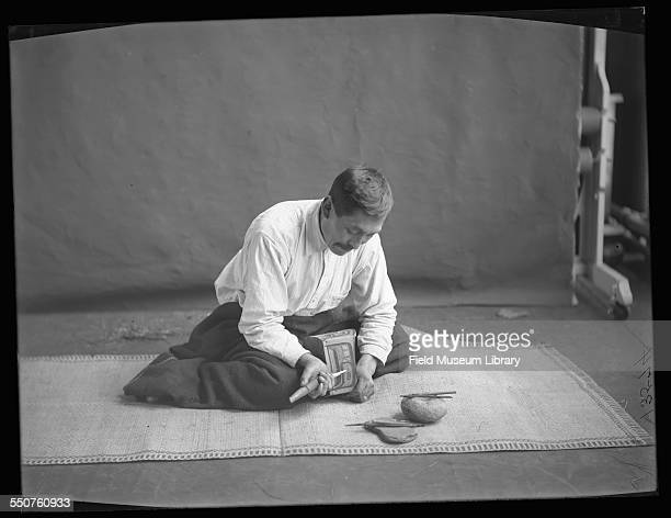 Portrait of First Nations Kwakiutl man Bob Harris seated on a mat and demonstrating the wood working and carving or painting of a bentwood box at the...