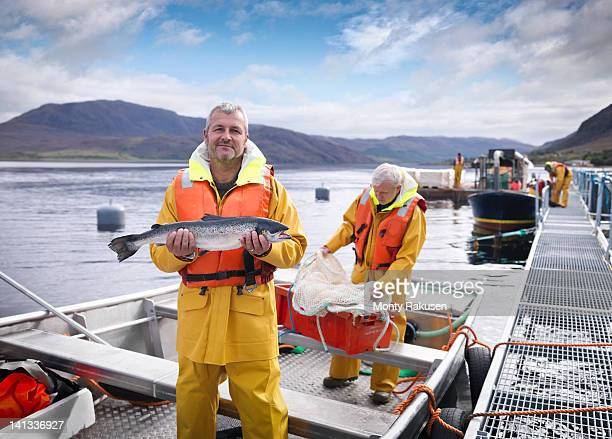 Portrait of fisherman with freshly caught salmon on loch of Scottish salmon farm