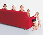 Portrait of Five Babies Around a Sofa