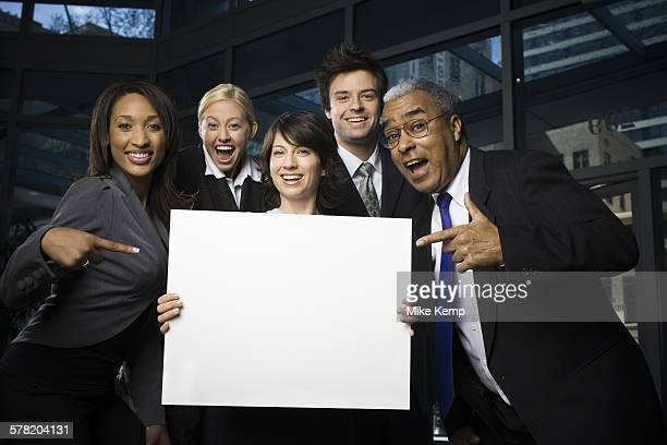 Portrait of five business executives standing with a blank sign