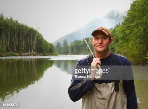 Portrait of fly fisherman standing in river : Stock Photo