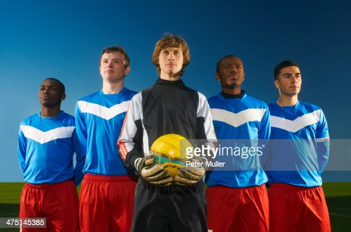 Portrait of football team, goalkeeper holding ball