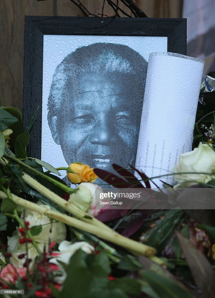 A portrait of former South African human rights leader and president Nelson Mandela lies under rain among flowers left by mourners outside the South African Embassy on December 9, 2013 in Berlin, Germany. Mandela died on December 5.