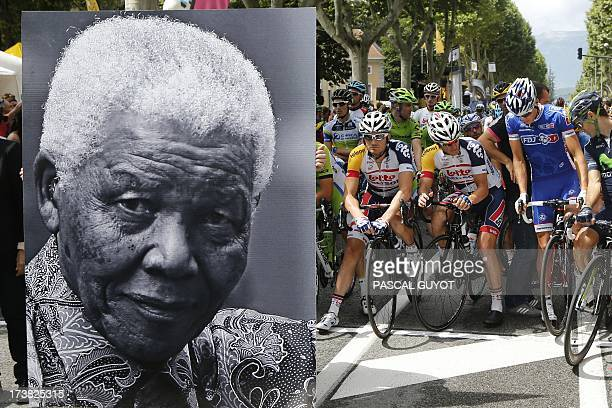 A portrait of former South African President Nelson Mandela is displayed in front of cyclists at the kilometer zero at the departure village to...