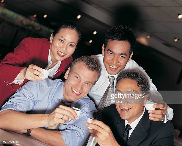 Portrait of Four Business Executives toasting With Saki in a Bar