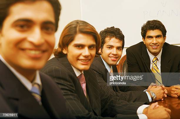 Portrait of four businessmen sitting in a conference room