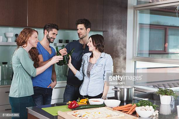 Portrait of four friends toasting with beer bottles in a kitchen