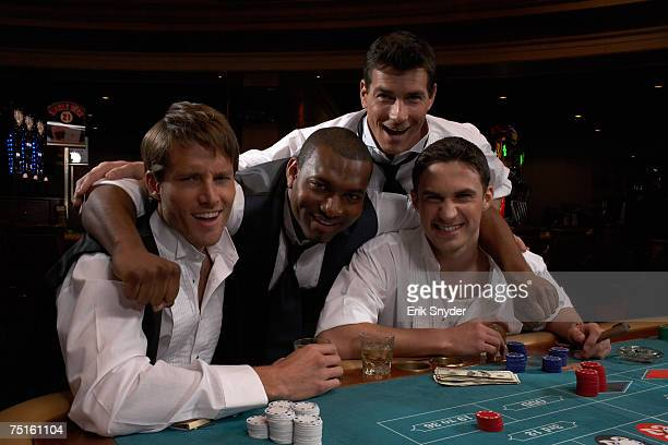 Portrait of four men sitting in casino playing roulette, smiling