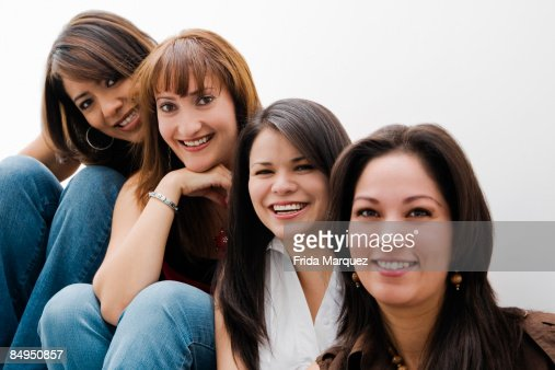 Portrait of four mid adult women sitting in a row and smiling