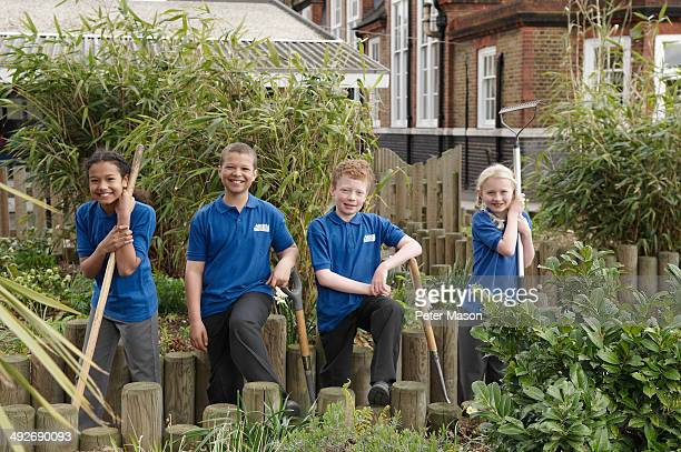 Portrait of four school children with gardening tools