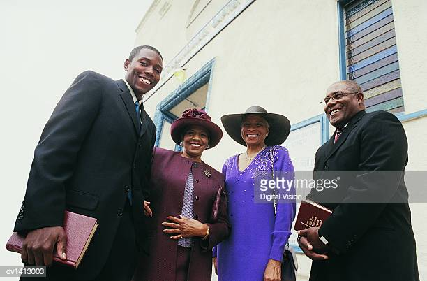 Portrait of Four Smiling People Standing Outside a Church With Their Bibles