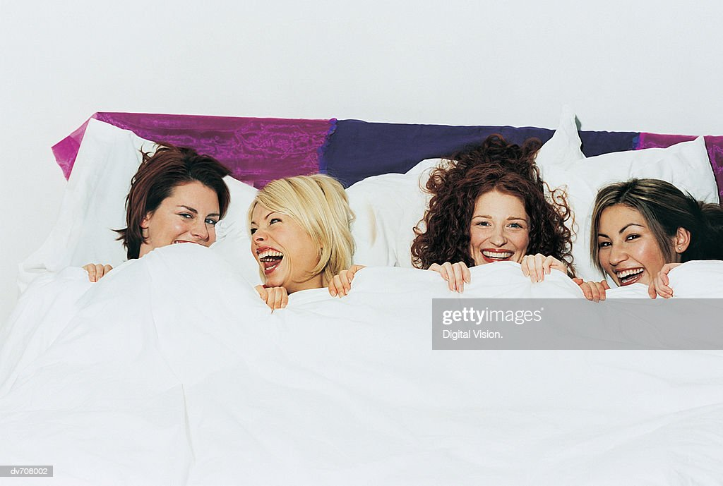 Portrait of Four Women Lying in Bed : Stock Photo