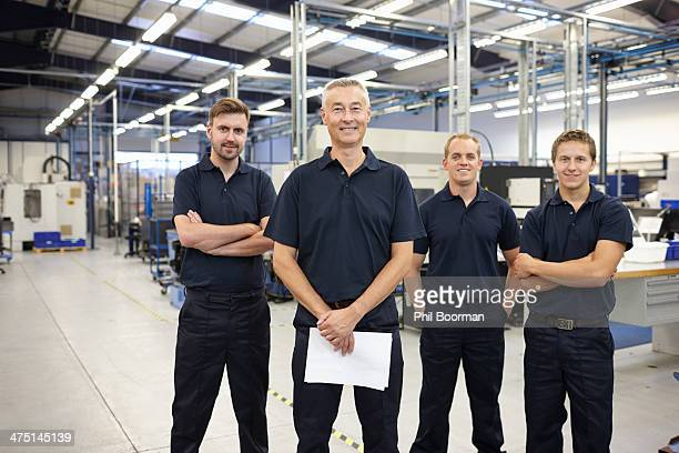 Portrait of four workers in engineering factory