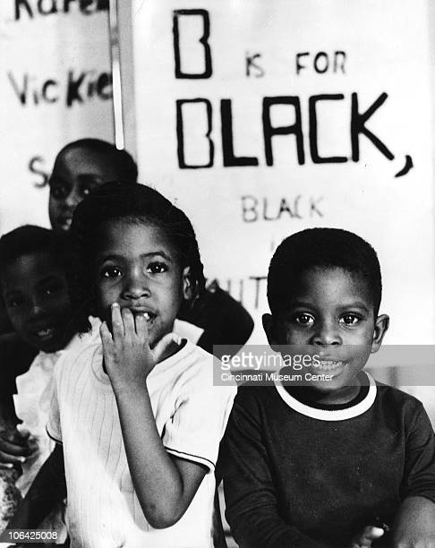Portrait of four young African American children posed in front of a handwritten sign that partially reads 'B is for Black' Cincinnati OH mid to late...