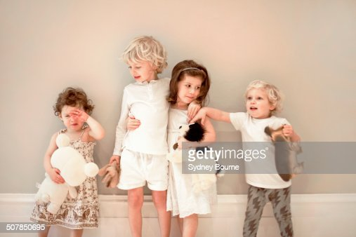 Portrait of four young children in a row, one crying
