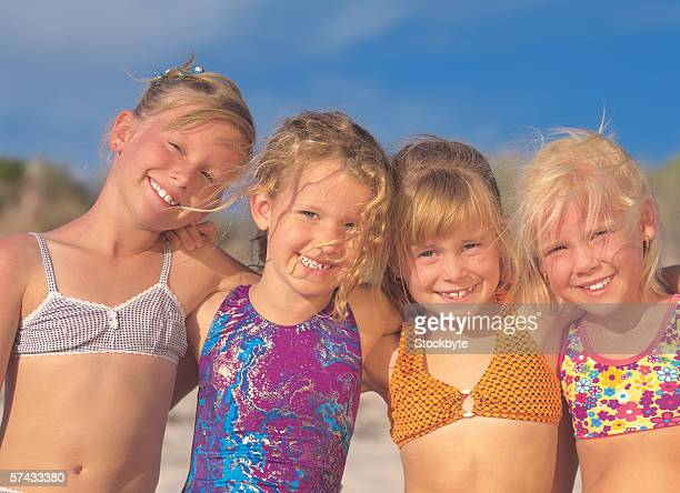 portrait of four young girl (6-8) wearing swimsuits and smiling on the beach