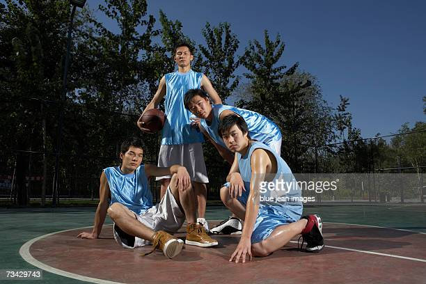 Portrait of four young men in blue jerseys on an outdoor basketball court, one holds a basketball.