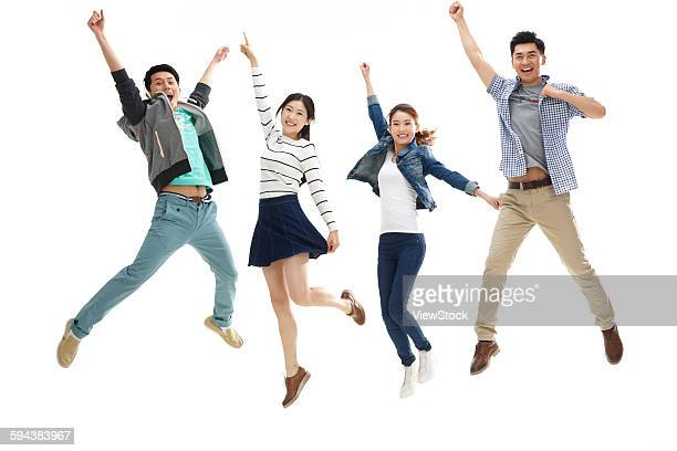 Portrait of four young people jumping
