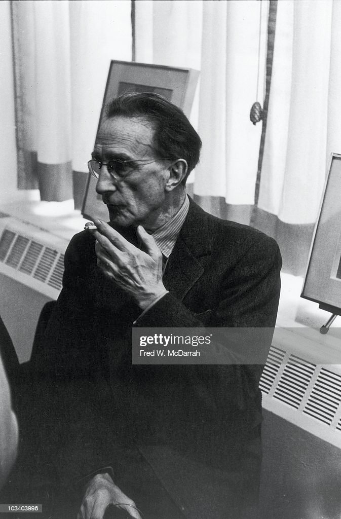 Portrait of French artist Marcel Duchamp as he smokes a cigarette in his home New York New York April 30 1963