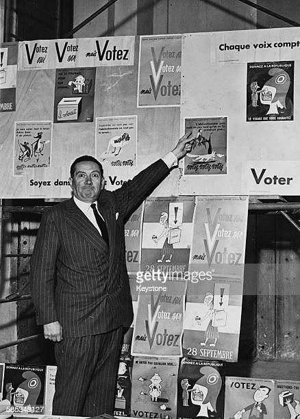 Portrait of French comedian Jean Rigaux pointing to some of the 'vote yes' posters for the referendum at the Grand Palais Paris September 25th 1958