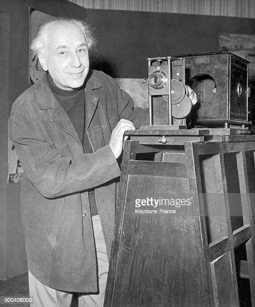 Portrait of French film director Abel Gance in front of an old projector model dating from the beginnings of cinema in November 1959
