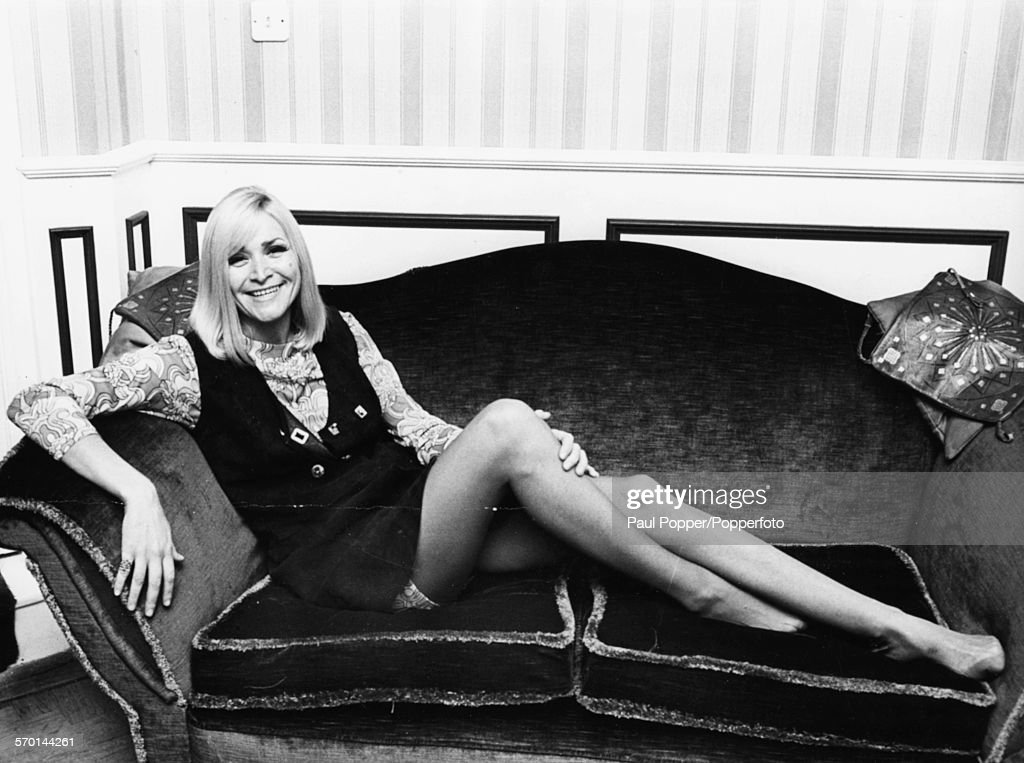 Portrait of French singer Jocelyne Jocya pictured sitting on a couch during a tour of Britain promoting her pop song 'Missing You' October 17th 1968